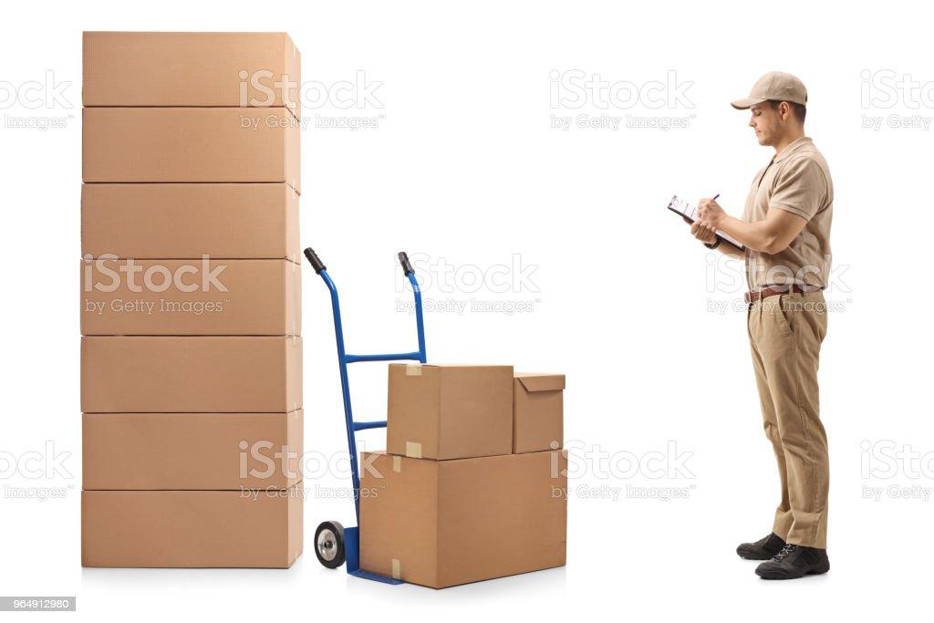 送貨人站在一輛手推車旁邊, 一堆箱子在剪貼簿上寫字。 - 免版稅30多歲圖庫照片