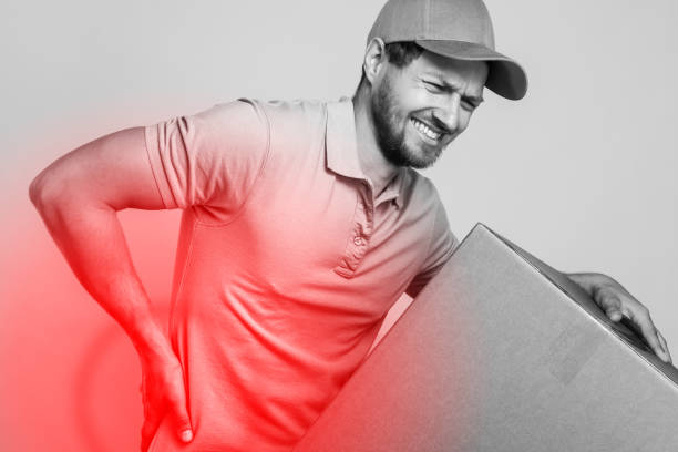 Delivery man suffering from a back pain while carrying heavy box stock photo