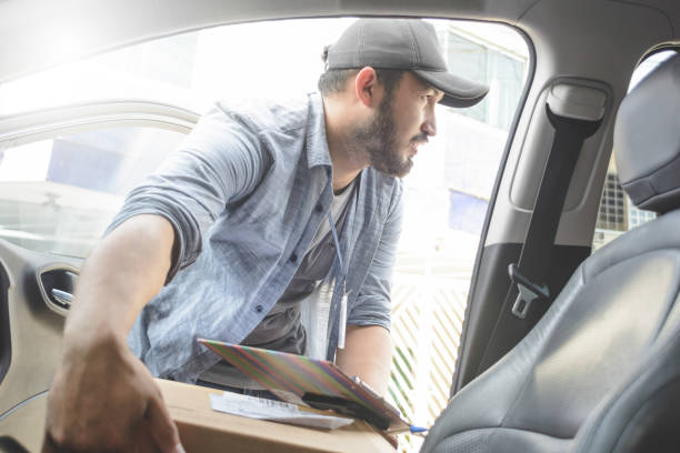 Delivery man taking out cardboard box from vehicle stock photo