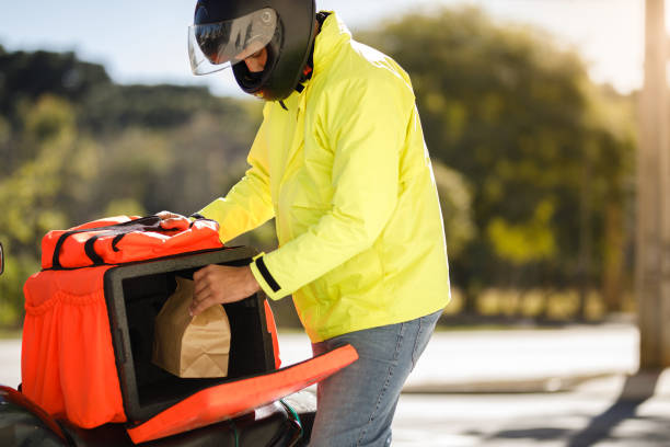 delivery man taking the order out of the backpack - motoboy stock photo