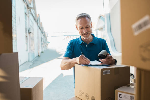 delivery man updating checklist - postal worker стоковые фото и изображения