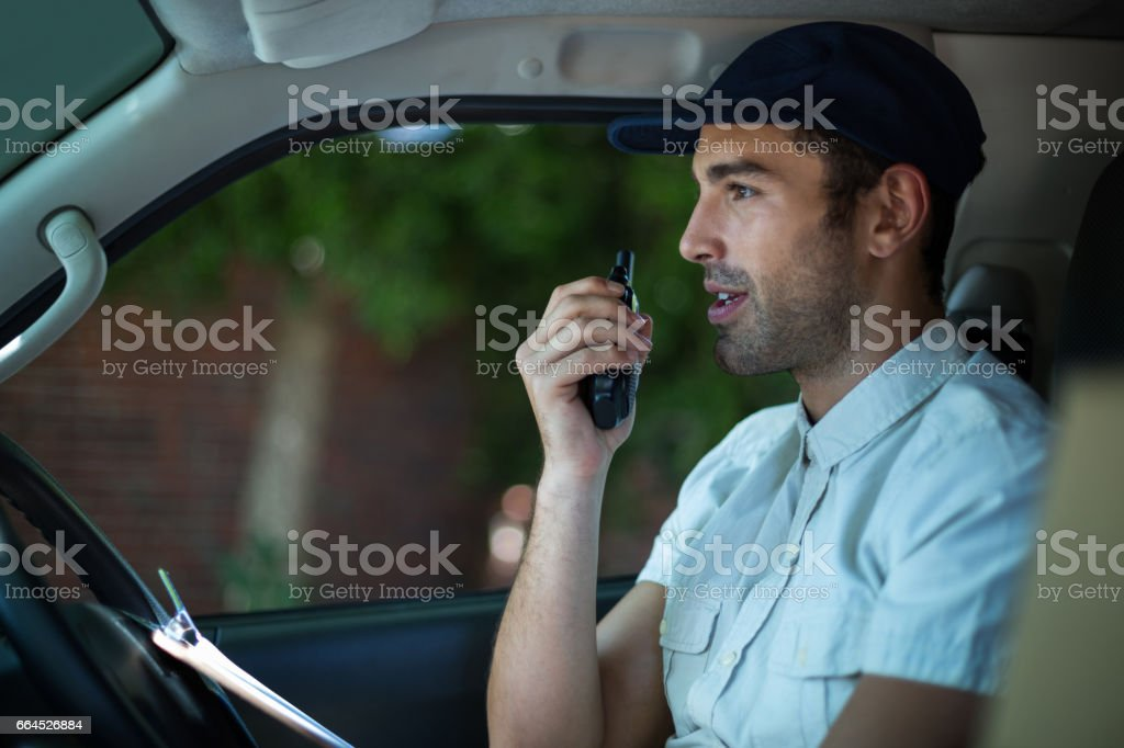 Delivery man using walkie-talkie royalty-free stock photo