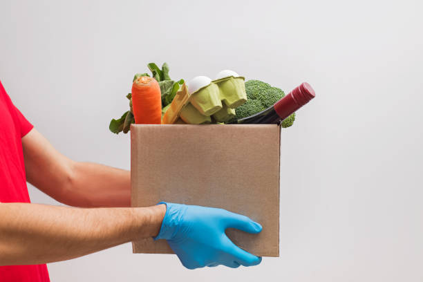 Delivery man wearing mask and gloves holding craft paper box full of different groceries. stock photo
