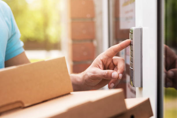 Delivery man with a packages is pressing buttons on a doorbell stock photo