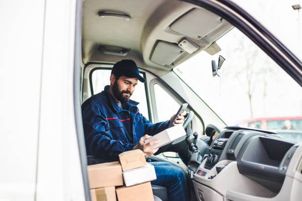 Delivery man with a parcel box in the car. stock photo