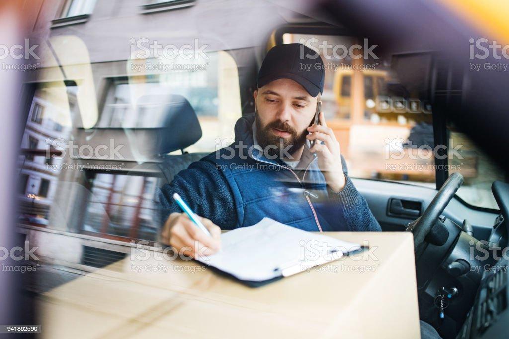 Lieferung Mann mit einer Paketbox im Auto. – Foto