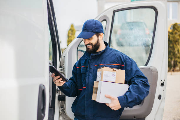 Delivery man with a parcel box in the car. - Stock image... Save stock photo