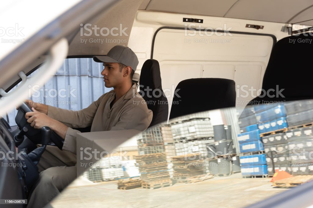 Side view of delivery man with cardboard boxes sitting in front seat...