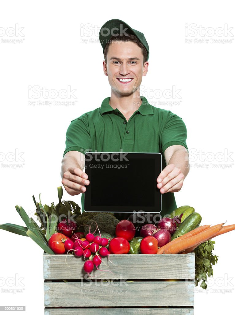 Delivery man with digital tablet Delivery man delivering box with organic food, holding digital tablet in hands and smiling at the camera. Studio shot, white background. Adult Stock Photo