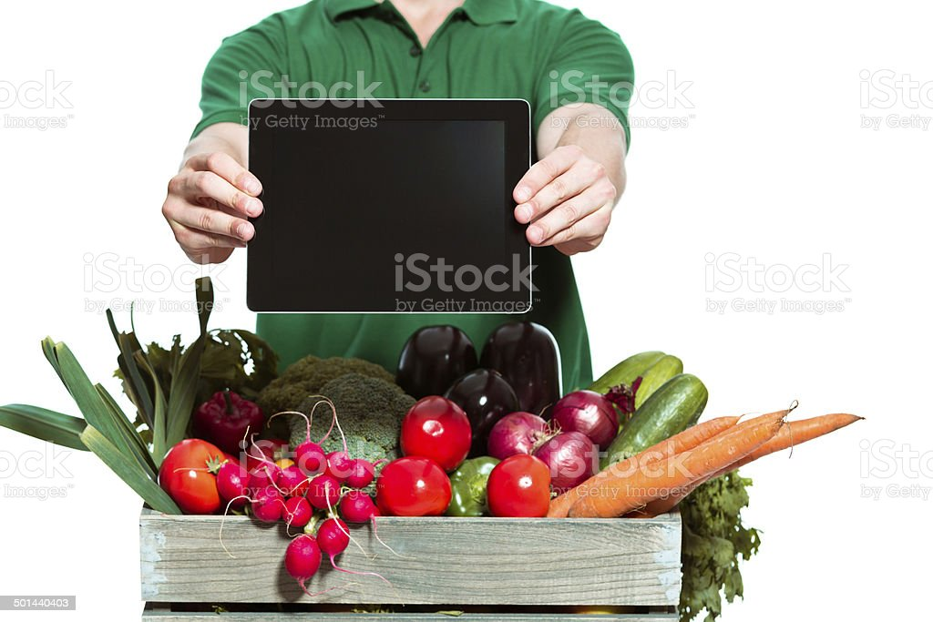 Delivery man with digital tablet Delivery man delivering box with organic food, holding digital tablet in hands. Close up of digital tablet. Studio shot, white background. Adult Stock Photo