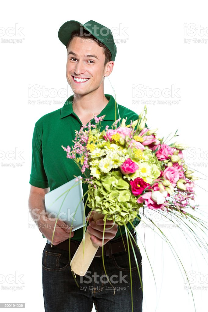 Delivery man with flowers Delivery man delivering flowers, holding digital tablet in hand and smiling at the camera. Studio shot, white background. Adult Stock Photo