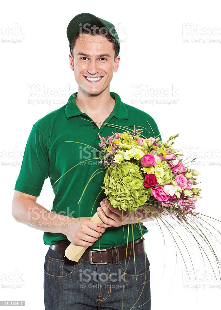 Delivery man with flowers Delivery man holding flowers and smiling at the camera. Studio shot, isolated on white. 2015 Stock Photo