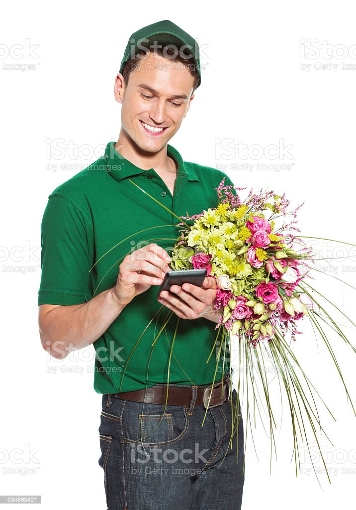 Delivery man with flowers Delivery man holding flowers and signing on palmtop. Studio shot, isolated on white. 2015 Stock Photo