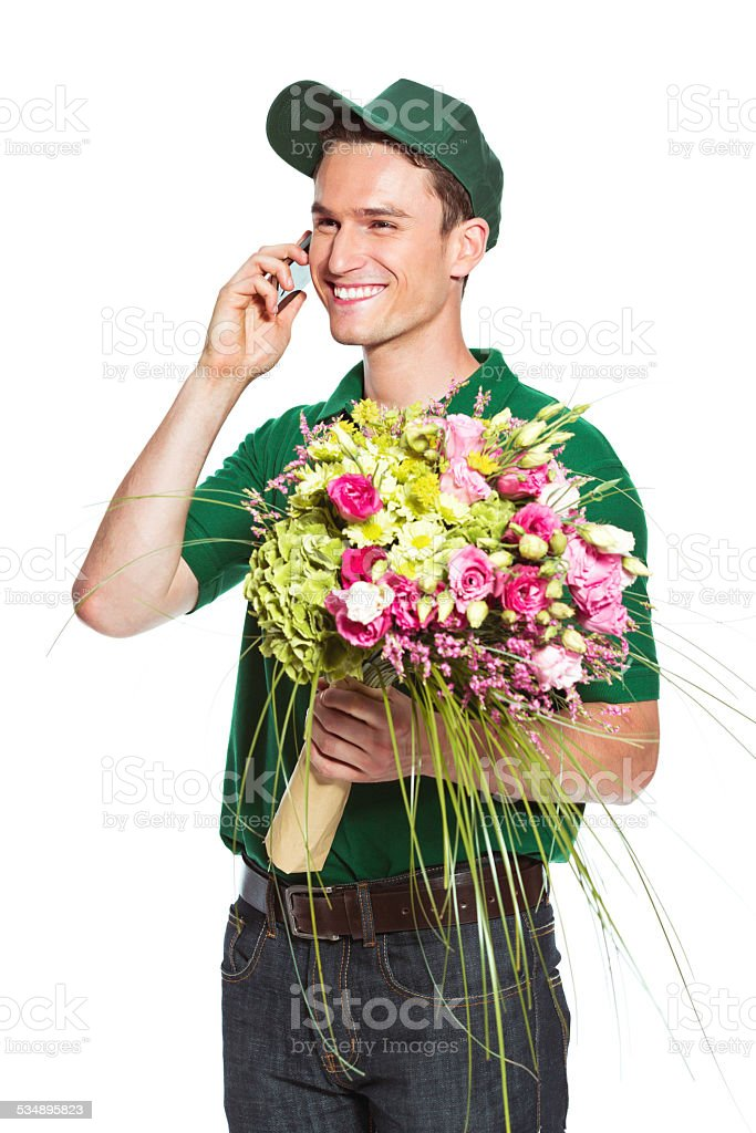 Delivery man with flowers, talking on phone Delivery man holding flowers and talking on cell phone. Studio shot, isolated on white. 2015 Stock Photo