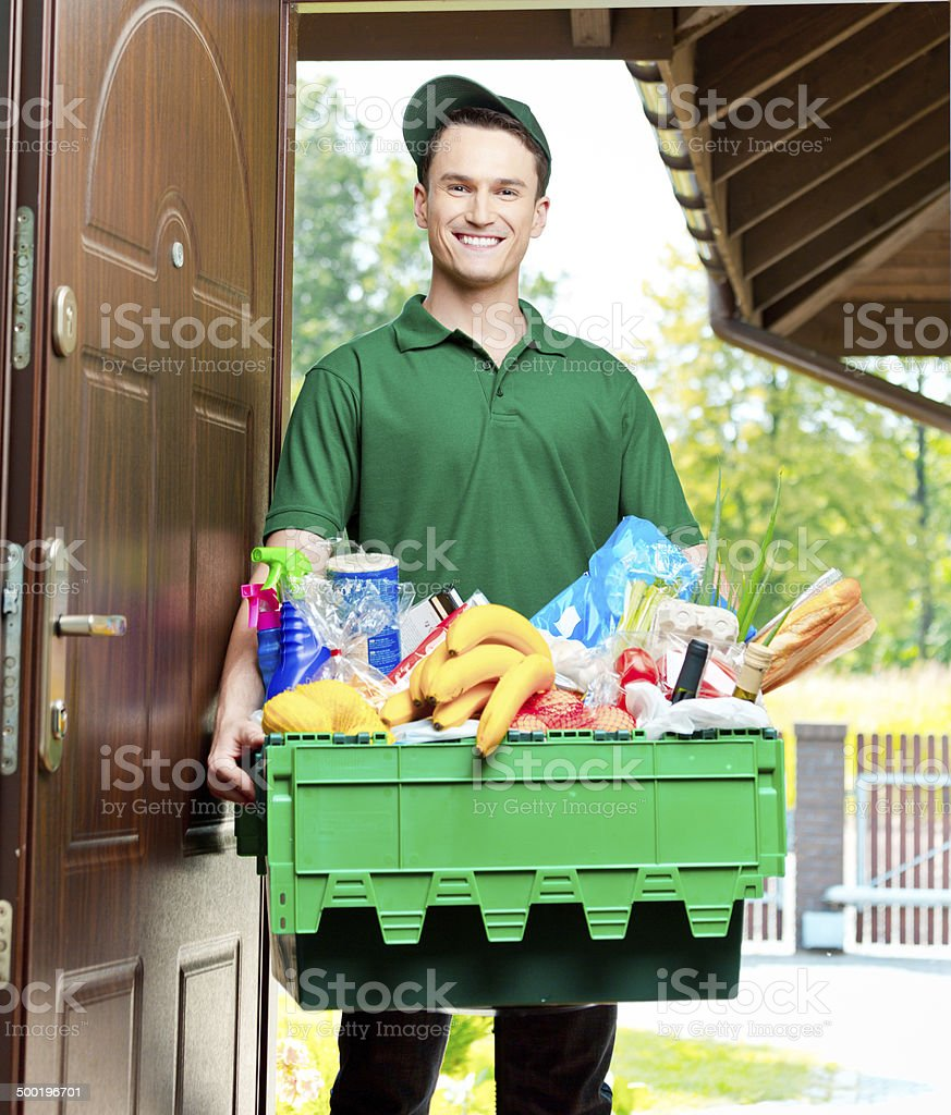 Delivery man with groceries Delivery man standing at the door of the house and carrying box with groceries, smiling at camera. Adult Stock Photo