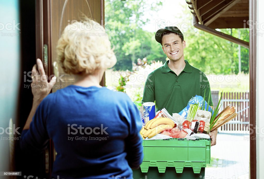 Delivery man with groceries Delivery man standing at the door of the house and carrying box with groceries, talking with senior woman. Active Seniors Stock Photo