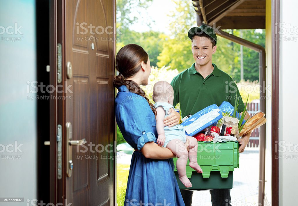 Delivery man with groceries Delivery man standing at the door of the house and carrying box with groceries, talking with woman holding baby. Adult Stock Photo
