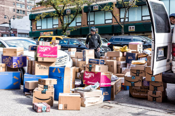 Delivery man with many boxes in NYC by BH photo video store, van truck unloading amazon prime, walmart, chewy, blue apron stock photo