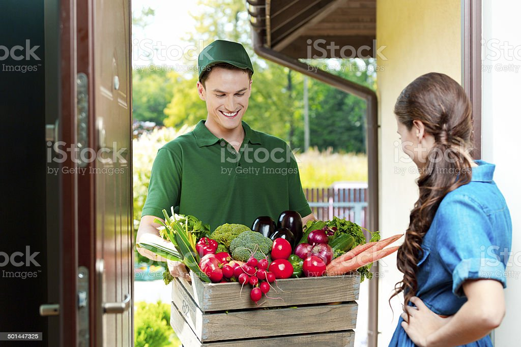 Delivery man with organic food Delivery man delivering to home box with organic food, talking with female customer. Adult Stock Photo