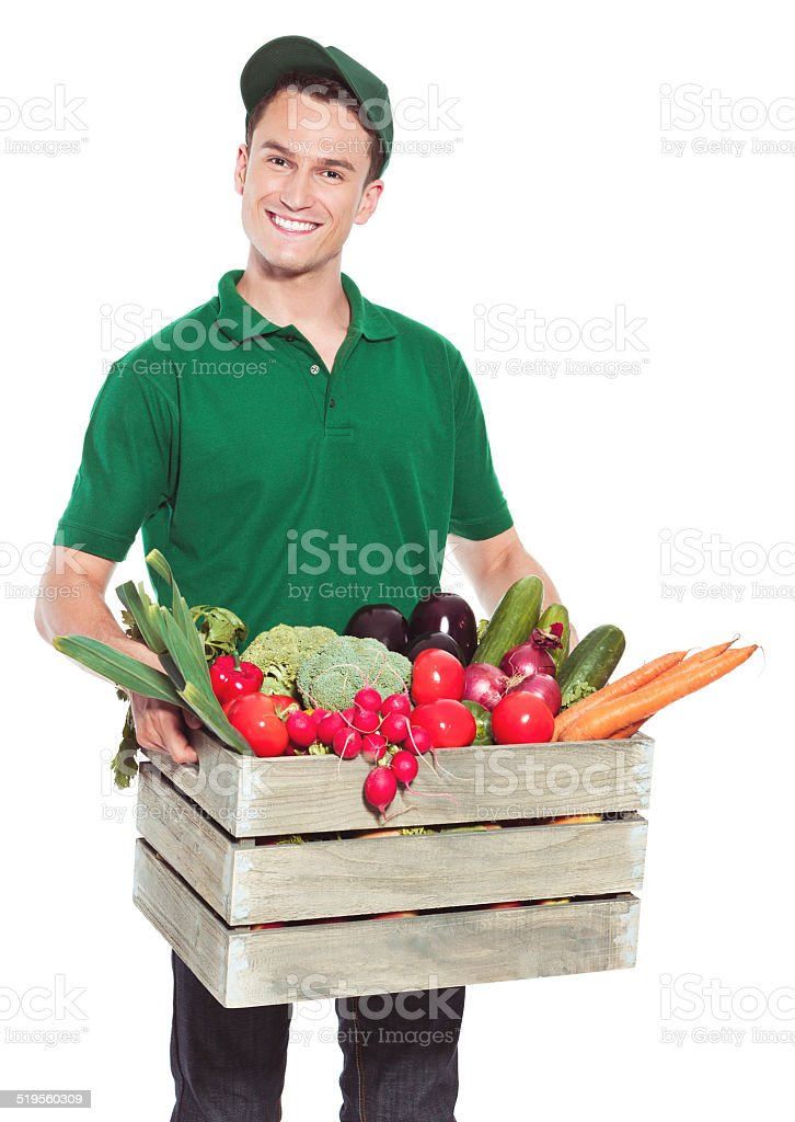 Delivery man with organic food Delivery man delivering box with organic food and smiling at the camera. Studio shot, white background. Adult Stock Photo