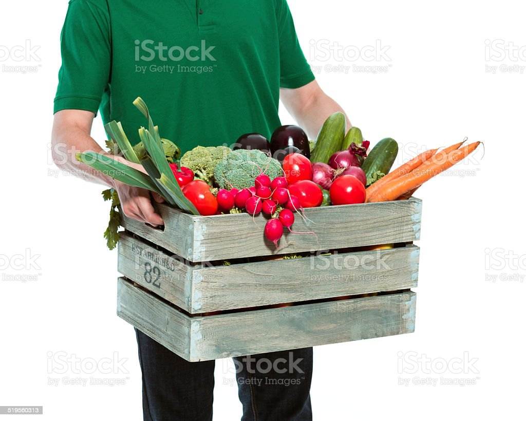 Delivery man with organic food Delivery man delivering box with organic food. Close up of box. Studio shot, white background. Adult Stock Photo