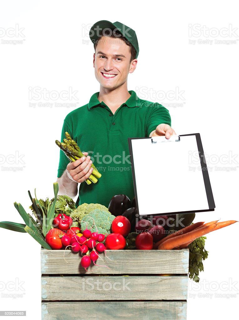 Delivery man with organic food Delivery man delivering box with organic food, holding clip board and asparagus in hands and smiling at the camera. Studio shot, white background. Adult Stock Photo