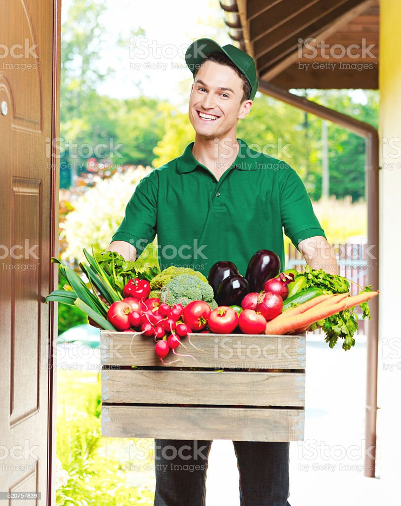 Delivery man with organic food Delivery man delivering box with organic food, standing in an entrance door and smiling at the camera. 20-24 Years Stock Photo