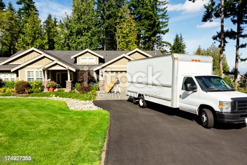 Photo of a delivery man moving cardboad boxes from truck to house with hand truck.