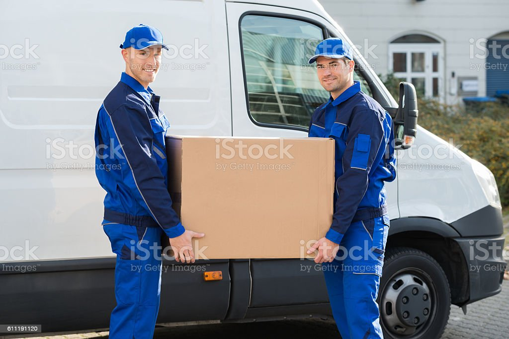 Delivery Men Carrying Cardboard Box Against Truck stock photo