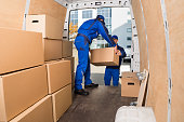 istock Delivery Men Loading Cardboard Boxes 600675074
