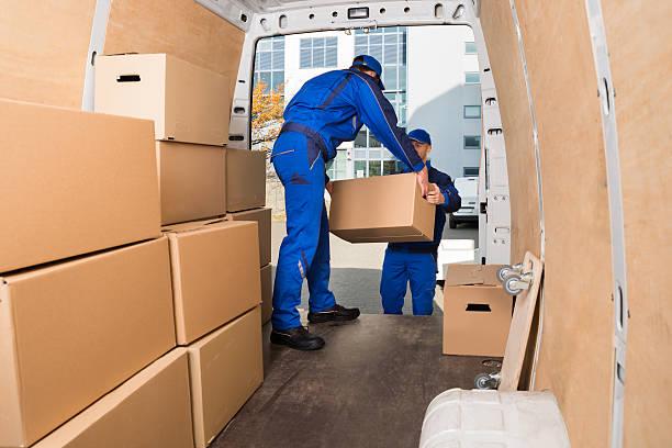 delivery men loading cardboard boxes - caricare attività foto e immagini stock