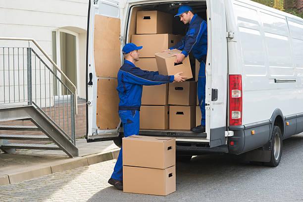delivery men unloading boxes from truck - umzug transport stock-fotos und bilder