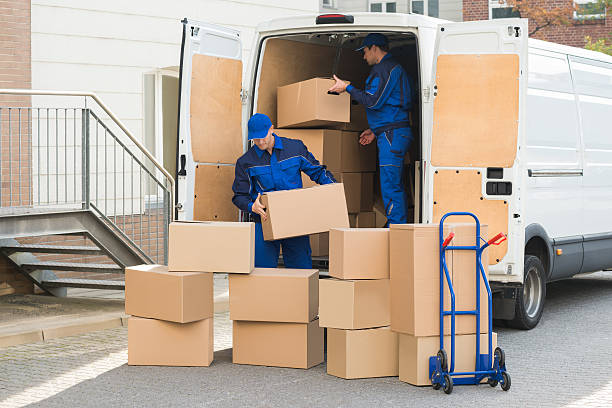 delivery men unloading boxes on street - umzug transport stock-fotos und bilder
