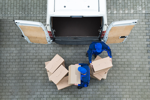 Delivery Men Unloading Cardboard Boxes From Truck On Street - 2人のストックフォトや画像を多数ご用意