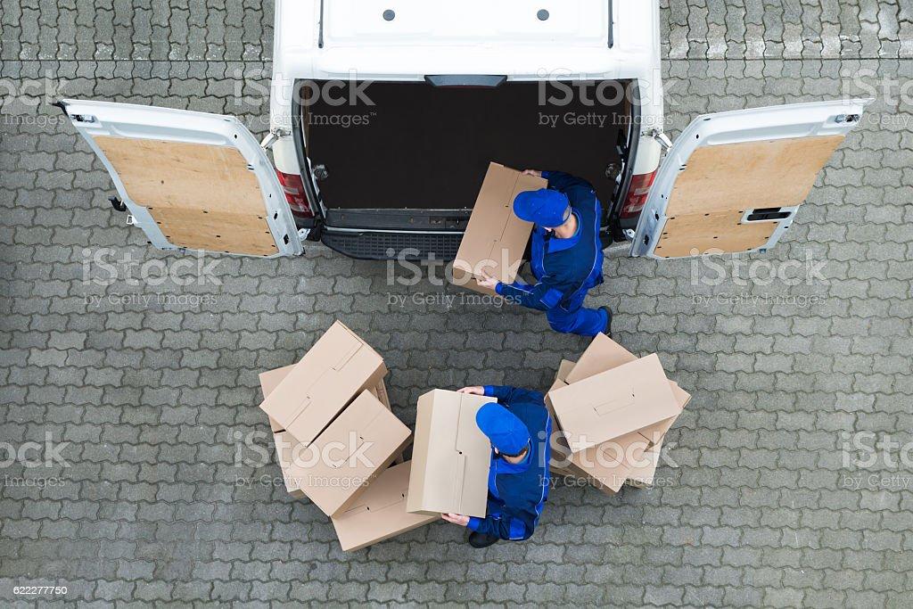 Delivery Men Unloading Cardboard Boxes From Truck On Street Lizenzfreies stock-foto