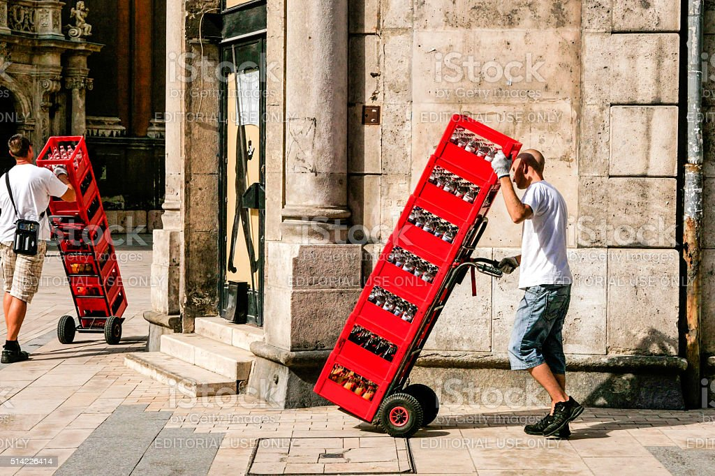 Delivery men wheeling red crates in Budapest, Hungary stock photo