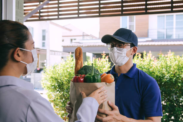 Delivery of asian man wearing a protective mask during an epidemic virus while he was delivering a bag of vegetable food to a female customer at the door. stock photo