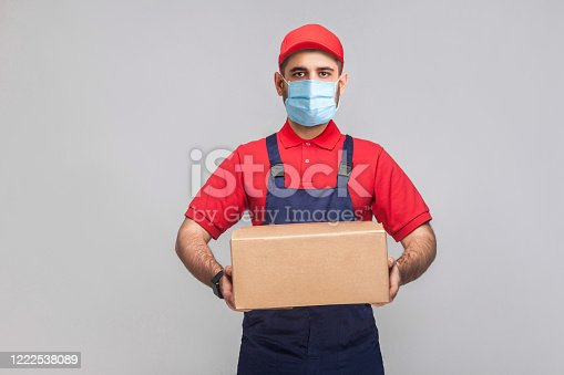 1047558948 istock photo Delivery on quarantine. Portrait of young man with surgical medical mask in blue uniform and red t-shirt standing and holding the cardboard box on grey background. 1222538089