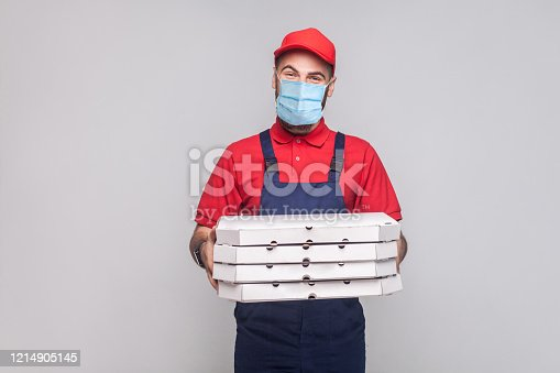 Delivery on quarantine. Young man with surgical medical mask in blue uniform and red t-shirt standing and holding stack of cardboard pizza boxes on grey background. Indoor, studio shot, isolated,