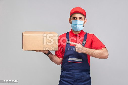 1047558948 istock photo Delivery on quarantine. Young man with surgical medical mask in blue uniform and red t-shirt standing, holding and pointing finger to cardboard box on grey background. 1222538098