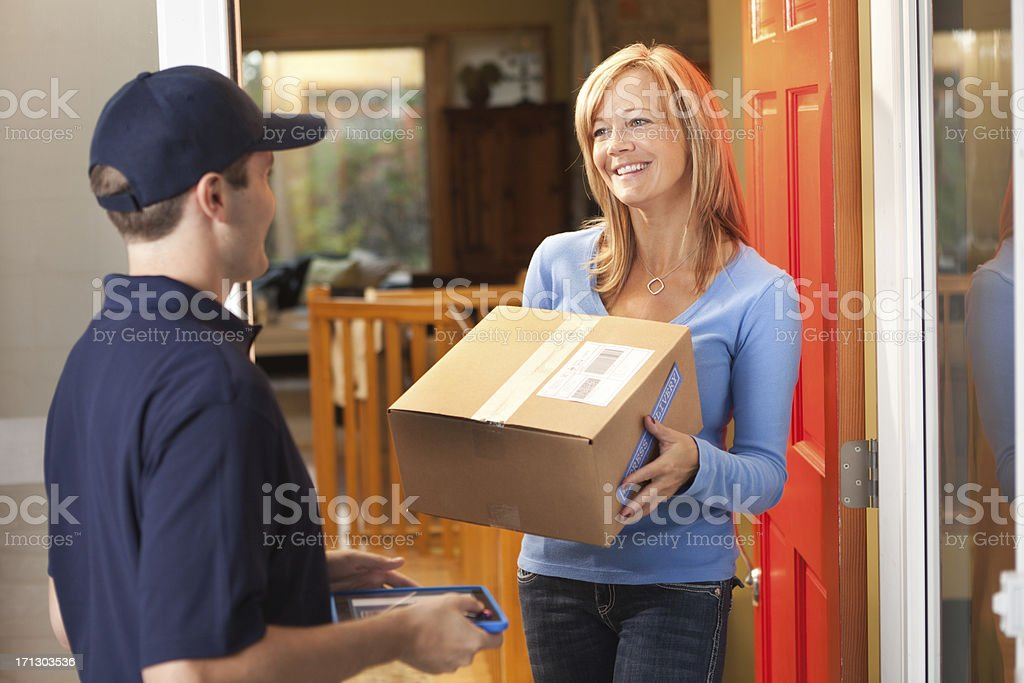 Delivery Person Delivering Box, Container Package to Residential Home stock photo