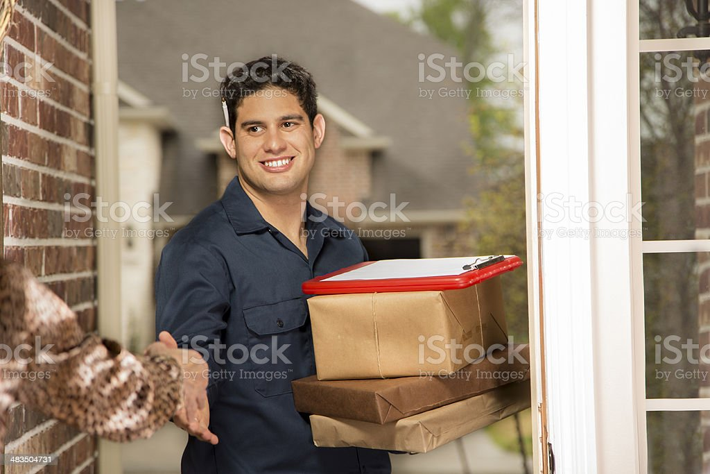 Latin descent man delivers packages to a customer\'s home. Delivery or...