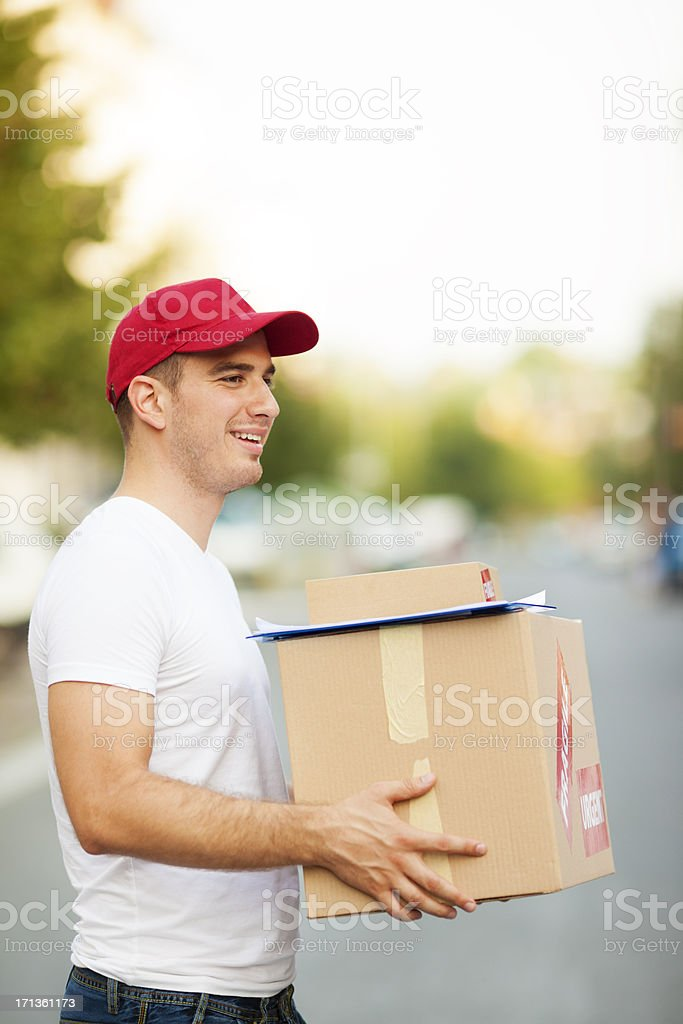 Delivery man holding packages, looking for address and smiling.