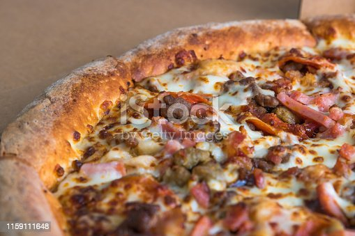 Close up view of a whole sliced delivery pizza pie. Sausage, ham, cheese, pepperoni, tomatoes, and barbeque sauce.