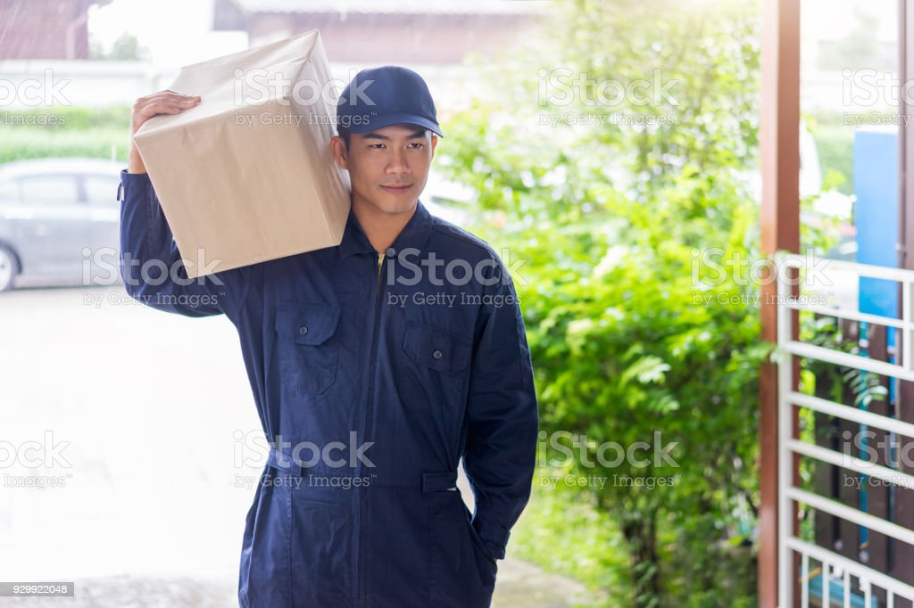 Delivery service company. Delivery man holding cardboard boxes,...
