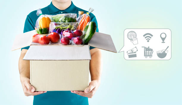 delivery service ingredients food for order online shopping and icon media symbol. delivery man in green uniform hand holding paper box package for grocery express service concept. - icona supermercato foto e immagini stock