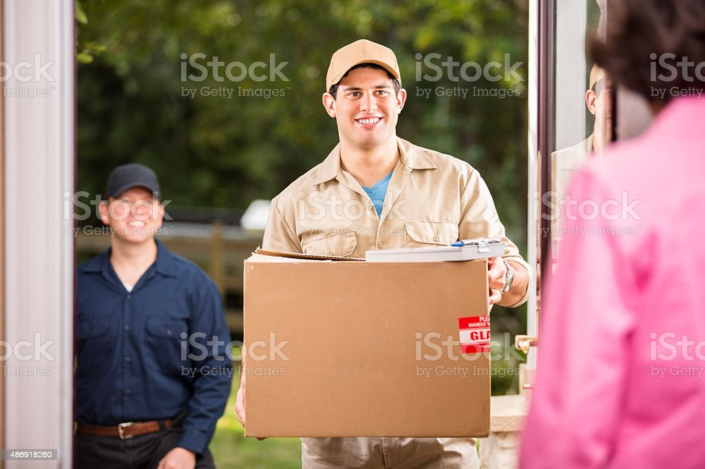 Home delivery service. Latin descent man and caucasian man deliver...