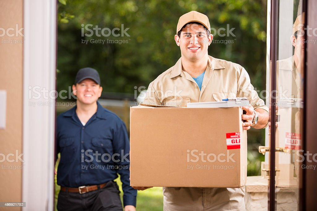 Delivery service. Latin man delivers package to customer. Home. Door. stock photo