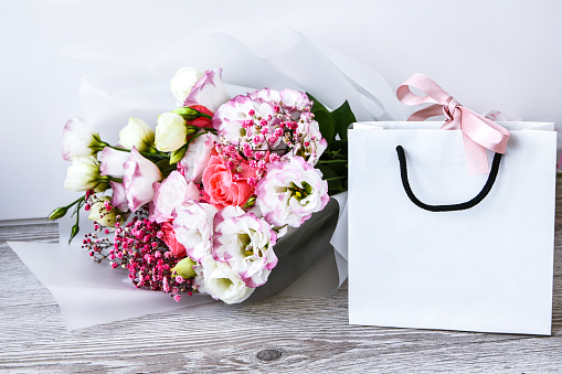delivery service packing bouquet flowers pink white background gift shipping. Beautiful romantic composition with flowers. St. Valentines Day background. white Eco bag present