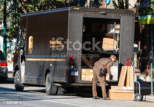 A UPS driver making deliveries in downtown Traverse City, Michigan. UPS is a package and letter delivery service with operations around the world.